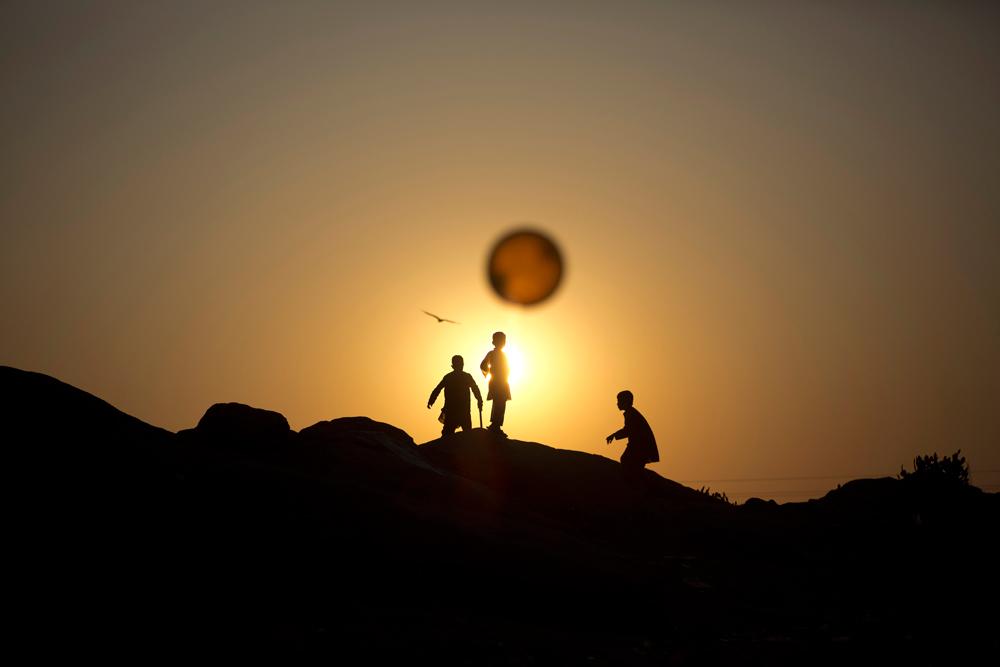 Bambini afgani rifugiati giocano a palla nei dintorni di Islamabad, in Pakistan. Muhammed Muheisen, Ap/Ansa