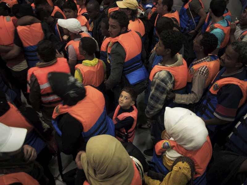 Un bambino in mezzo a un gruppo di adulti soccorso nel Mediterraneo nel 2014 (foto UNHCR).