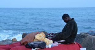 Un migrante sugli scogli di Ventimiglia.
